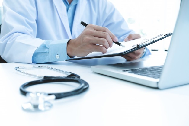 doctor-working-with-laptop-computer-and-writing-on-paperwork-hospital-background_1421-69